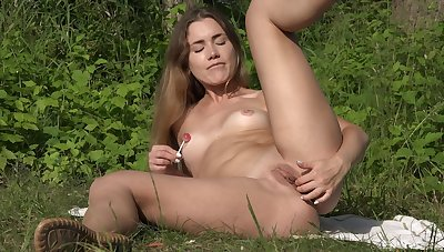 Teen pleases her shaved pussy with soft touches and a lollipop
